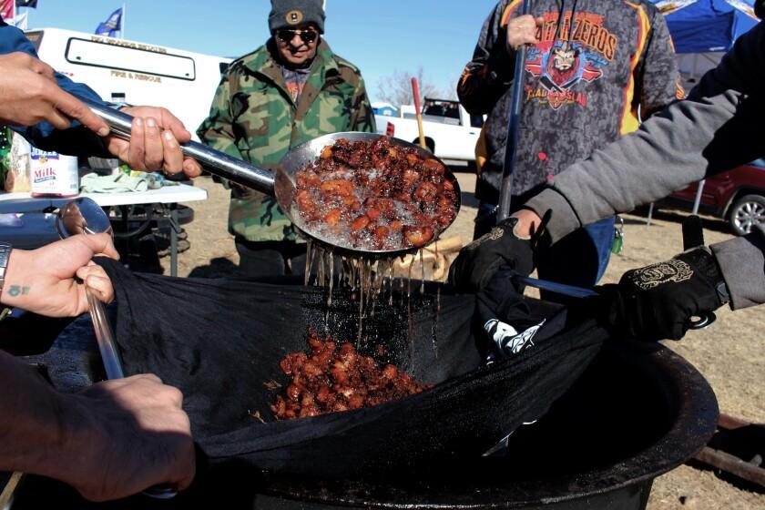 The Matanzeros strain out the lard from chicharrones. (Gustavo Arellano / Los Angeles Times)