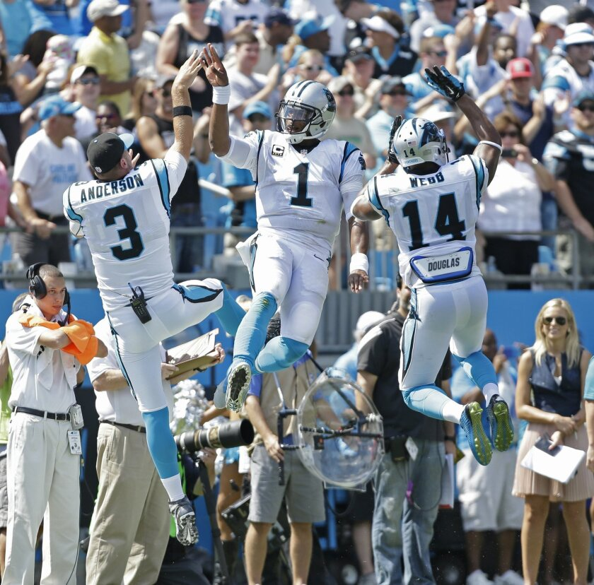 Carolina Panthers' Cam Newton (1) celebrates his touchdown pass with Derek Anderson (3) and Joe Webb (14) during the first half of an NFL football game against the Houston Texans in Charlotte, N.C., Sunday, Sept. 20, 2015. (AP Photo/Bob Leverone)