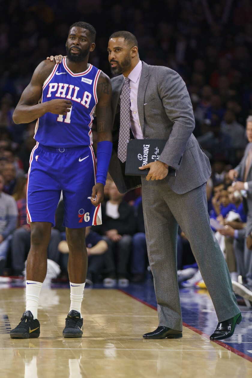 File-This Nov. 20, 2019, file photo shows Philadelphia 76ers' James Ennis III, left, talking things over with assistant coach Ime Udoka, right, during the second half of an NBA basketball game against the New York Knicks, in Philadelphia. The Boston Celtics have hired Brooklyn Nets assistant Ime Udoka to be their new coach, a person familiar with the decision told The Associated Press on Wednesday, June 23, 2021. The person spoke on the condition of anonymity because the deal had not been announced. (AP Photo/Chris Szagola, File)