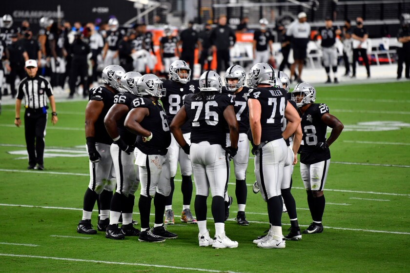 The Las Vegas Raiders huddle between plays against the New Orleans Saints.