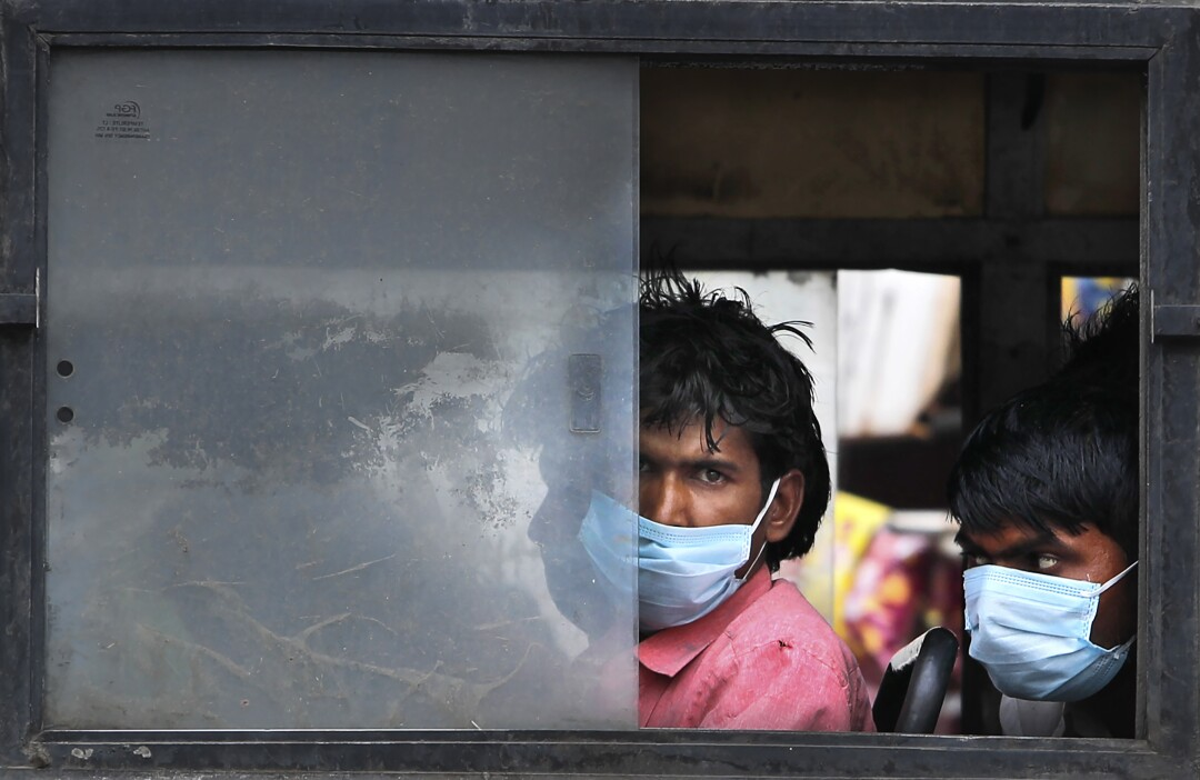 Migrant laborers travel in a bus.
