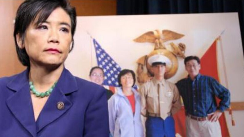 Rep. Judy Chu stands in front of a photo of her nephew, Lance Cpl. Harry Lew, and his family.