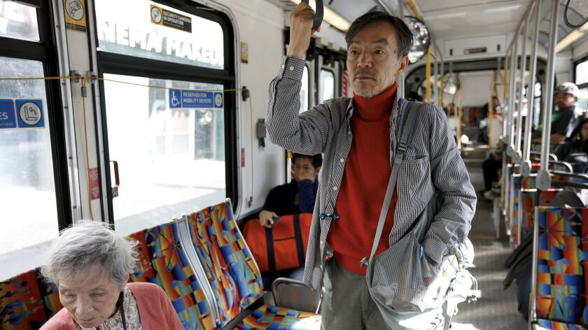 Seon Jin Kim, standing, rides the bus to choir practice at St. James Episcopal Church in Los Angeles