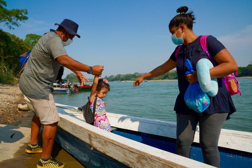 A man helps a child into a boat that a woman is standing in.
