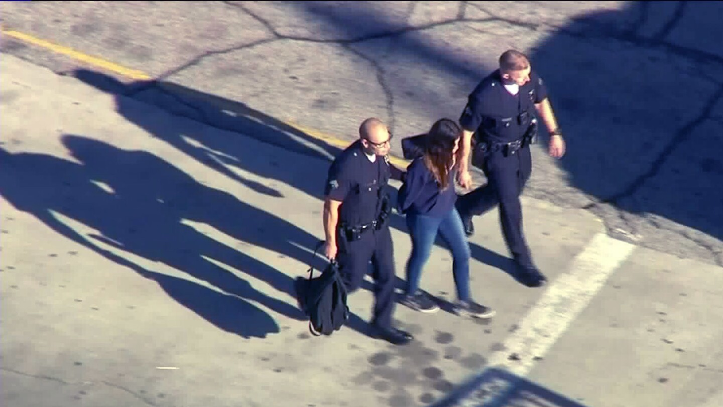 Police take a girl into custody on the campus of Salvador Castro Middle School in Los Angeles following a shooting in which two students were hit by gunfire.