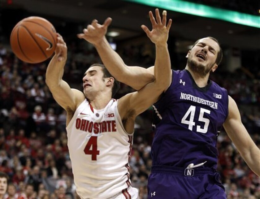 Ohio State's Aaron Craft, left, and Northwestern's Nikola Cerina reach for a rebound during the first half of an NCAA college basketball game in Columbus, Ohio, Thursday, Feb. 14, 2013. (AP Photo/Paul Vernon)