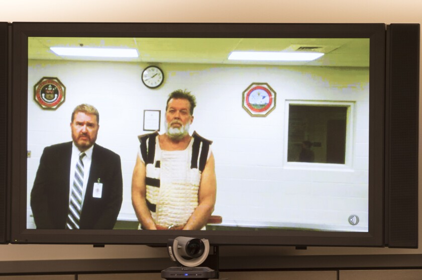 Colorado Springs Planned Parenthood shooting suspect Robert Dear, shown with public defender Dan King, appears via video hearing during his first court appearance, where he was told he will be charged with first-degree murder.