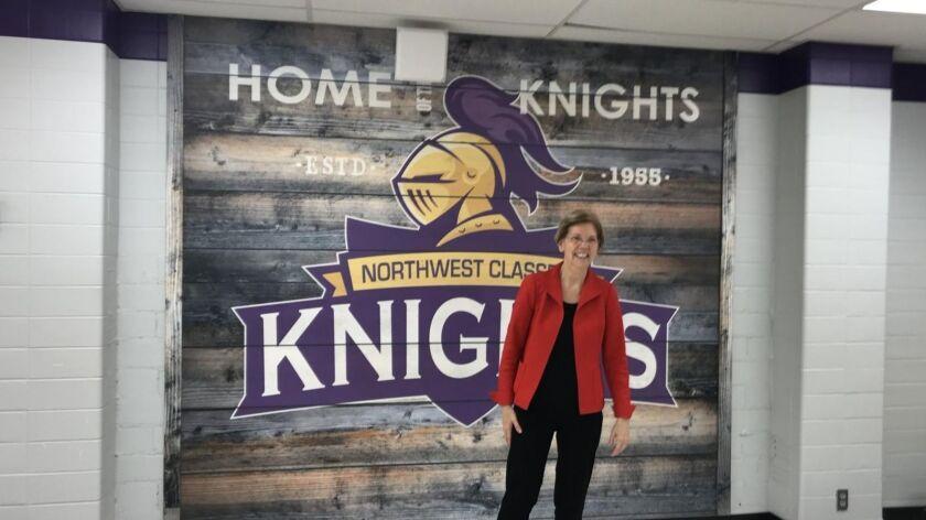 Sen. Elizabeth Warren poses in front of her high school seal