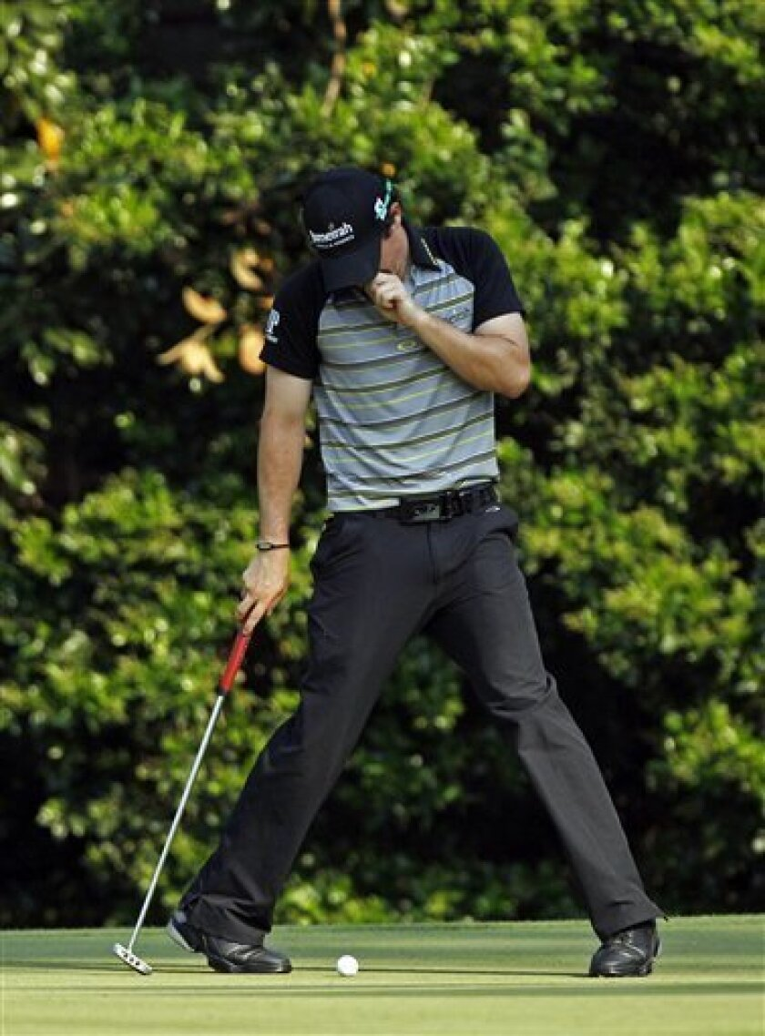 Rory McIlroy of Northern Ireland stands over his ball before putting the 11th hole during the final round of the Masters golf tournament Sunday, April 10, 2011, in Augusta, Ga. McIlroy bogeyed the hole. (AP Photo/Matt Slocum)