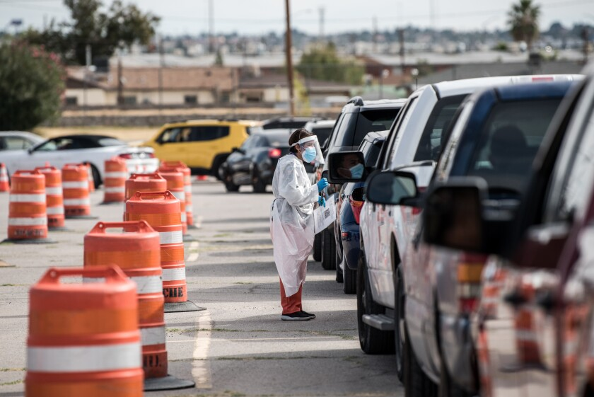 An attendant talks to a motorist at a coronavirus testing site at Ascarate Park in El Paso.