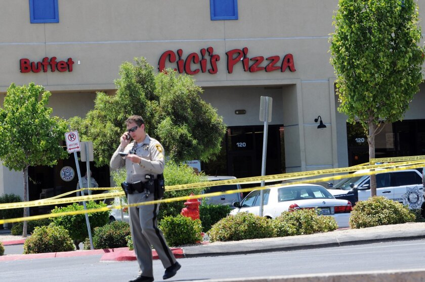 A Las Vegas police officer walks near the scene of a shooting in Las Vegas, Sunday, June 8, 2014. The spree began around 11:30 a.m. Sunday when a man and woman walked into CiCi's Pizza and shot two officers who were eating lunch, Las Vegas police spokesman Larry Hadfield said. (AP Photo/Las Vegas Review-Journal, Eric Verduzco)