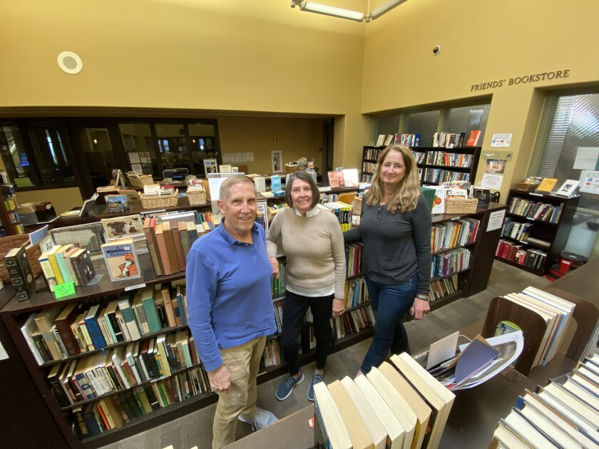 Volunteers Jim Stewart, Suzanne Weiner and Kara Farley pose in front of some of the hundreds of books they have for sale at the Friends of La Jolla Library bookstore, 7555 Draper Ave.
