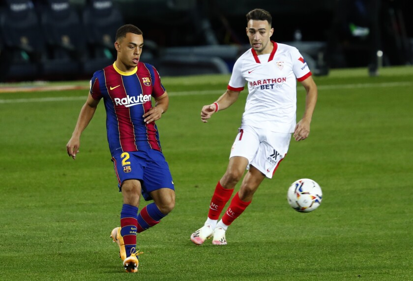 Barcelona's Sergino Dest fights for the ball against Sevilla's Suso during the Spanish La Liga soccer match between FC Barcelona and Sevilla FC at the Camp Nou stadium in Barcelona, Spain, Sunday, Oct. 4, 2020. (AP Photo/Joan Monfort)