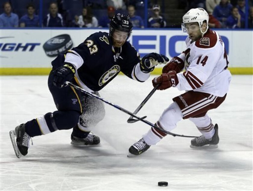 St. Louis Blues' Jordan Leopold, left, and Phoenix Coyotes' Chris Conner chase after a loose puck during the first period of an NHL hockey game on Thursday, April 18, 2013, in St. Louis. (AP Photo/Jeff Roberson)