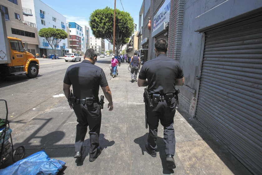LAPD officers patrol skid row in downtown L.A. in July; a new report by the LAPD inspector general has found the department falsified records to make it appear that it was meeting staffing standards for officers on street patrol.
