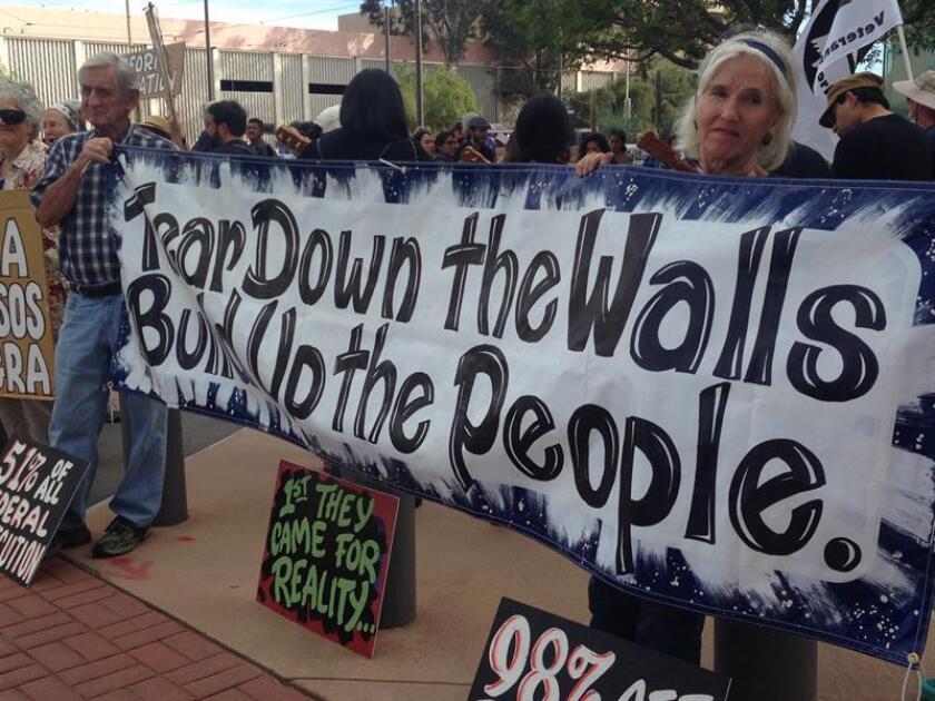 Vista de varias personas que protestan en contra de la persecución a los indocumentados. EFE/Archivo