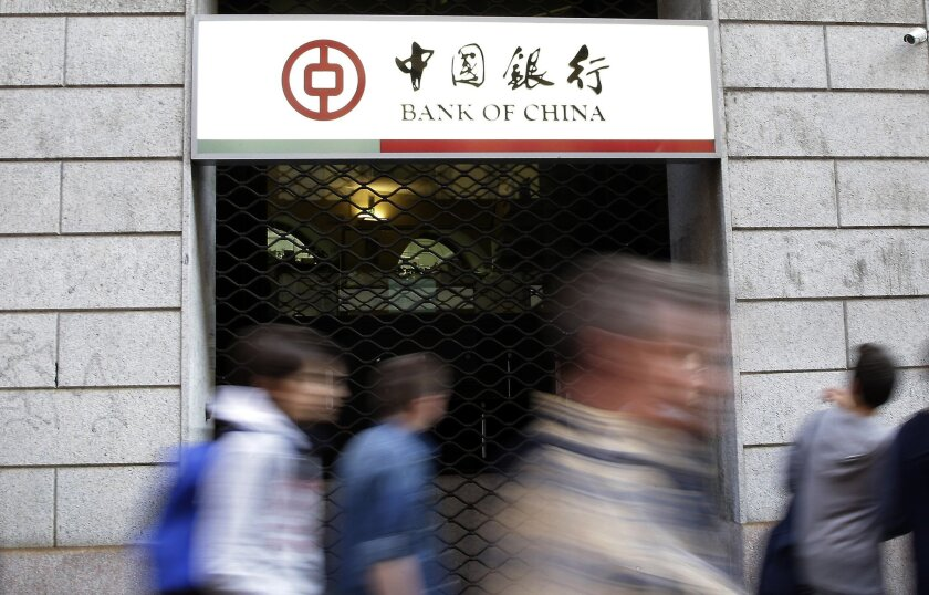In this photo taken Wednesday, April 15, 2015, residents walk past the Bank of China branch in downtown Milan, Italy. Italian prosecutors say more than 4.5 billion euros ($4.9 billion) were smuggled to China in less than four years – nearly half of it with the help of the state – run Bank of China.