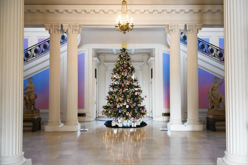 "Installation view of the mansion's grand staircase with the holiday tree decorated in Alex Israel self-portrait ornaments, with ""Sky Backdrop Mural,"" 2015, on the staircase walls."