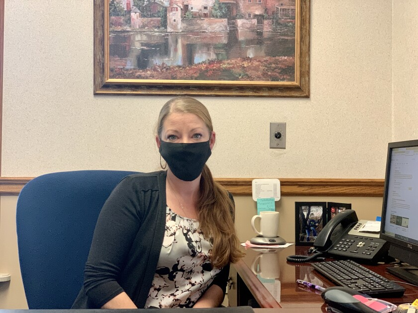 Jami Colich wears a mask while sitting at her office desk