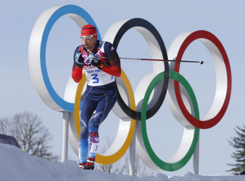 FILE - In this Feb. 23, 2014 file photo Russia's gold medal winner Alexander Legkov skis past the Olympic rings during the men's 50K cross-country race at the 2014 Winter Olympics in Krasnaya Polyana, Russia. The Court of Arbitration for Sport ruled on Thursday, Feb. 1, 2018 to reinstate Leskov as gold medal winner of the men's 50-kilometer cross-country skiing which he was stripped of on doping allegations earlier.