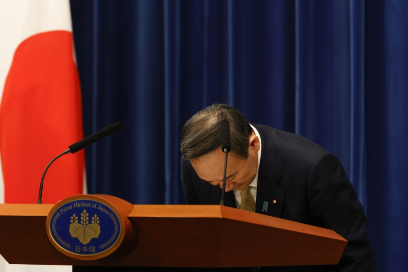 Japan's Prime Minister Yoshihide Suga bows during a press conference at the prime minister's official residence Wednesday, Jan. 13, 2021, Tokyo, Japan. Suga announced that Japan has expanded a coronavirus state of emergency for seven more prefectures Wednesday, affecting more than half the population amid a surge in infections across the country. (Rodrigo Reyes Marin/Pool Photo via AP)