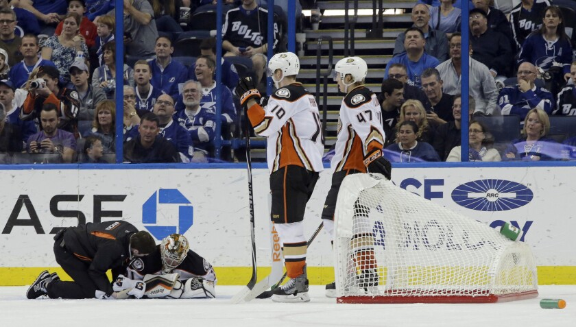 Ducks right wing Corey Perry and defenseman Hampus Lindholm look on as goalie Frederik Andersen is tended to by a trainer Sunday night at Tampa Bay.