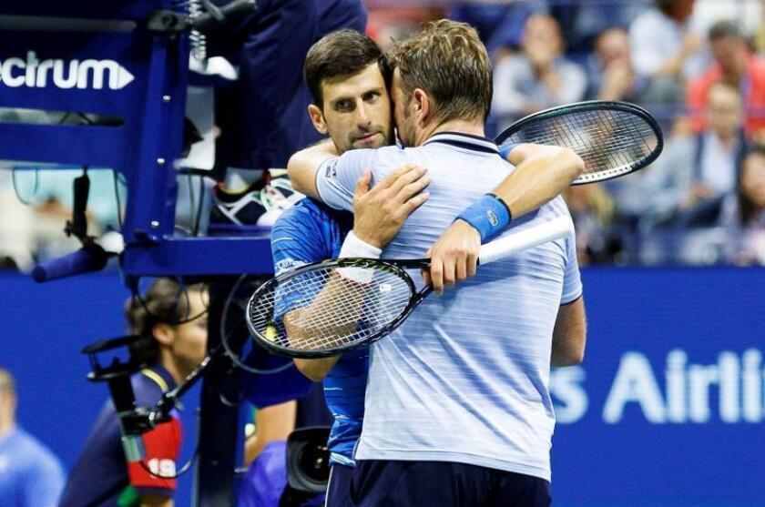 El tenista serbio Novak Djokovic (i) fue registrado este domingo al abrazar al suizo Stan Wawrinka (d), luego de que Djokovic tuviera que retirarse por lesión de un partido de la tercera ronda del Abierto de Estados Unidos, en el USTA National Tennis Center de Flushing Meadows (Nueva York, EE.UU.). EFE/Justin Lane