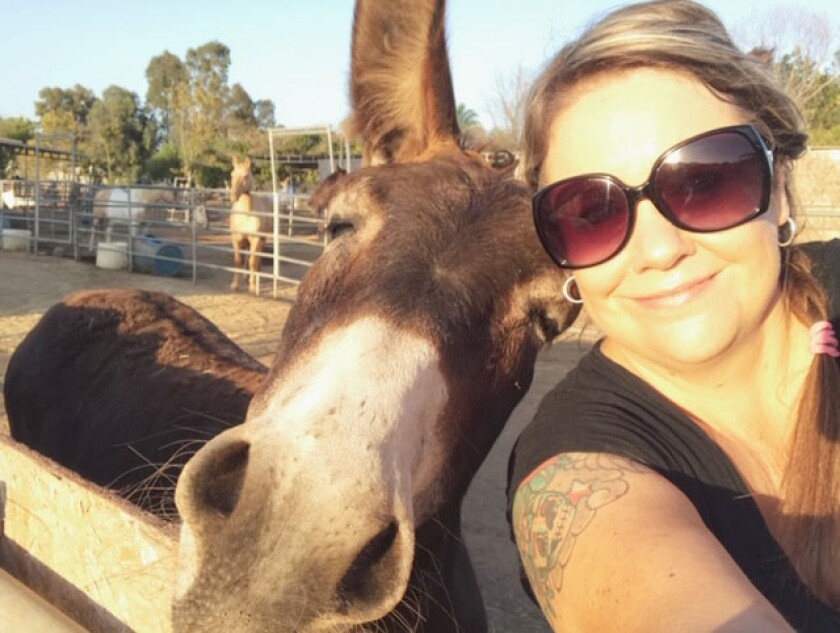 Rescue Administrative Assistant Lisa Claar nuzzles with rescue resident Pedro.