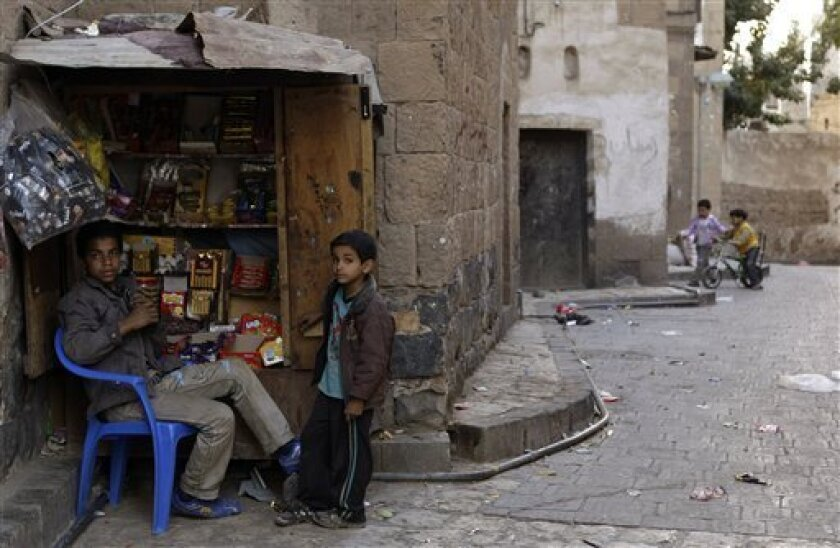 Yemeni vendor Hassan Azany, 19, left sits by his makeshift shop at an alley in the old city of Sanaa, Yemen Tuesday, Jan. 3, 2012. (AP Photo/Hani Mohammed)