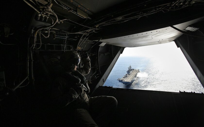Dawn Blitz 2015, a multinational amphibious training exercise is being conducted on and off Camp Pendleton,Naval Base San Diego and a MCAGCT at Twenty-nine Palms, CA. involving US forces, Japan, New Zealand and Mexico.  Marine Cpl Logan Horne, crew chief aboard a SV-22 Osprey, watches the USS Boxer