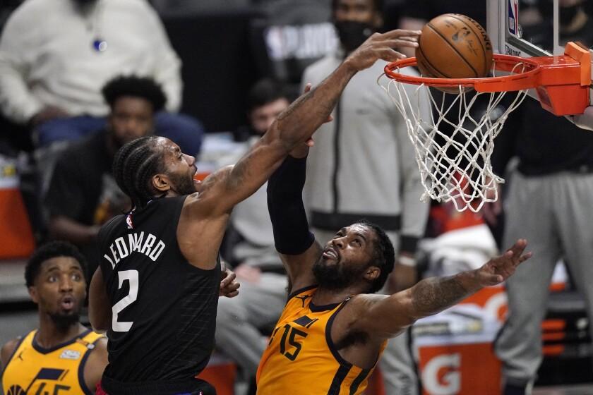 El jugador de los Clippers de Los Ángeles Kawhi Leonard, en el centro, hace una clavada por encima del jugador del Jazz de Utah Derrick Favors, a la derecha, mientras Donovan Mitchell mira, en la primera mitadl del Cuarto juego de su serie de segunda ronda de playoffs de la NBA, el lunes 14 de junio de 2021 en Los Ángeles. (AP Foto/Mark J. Terrill)