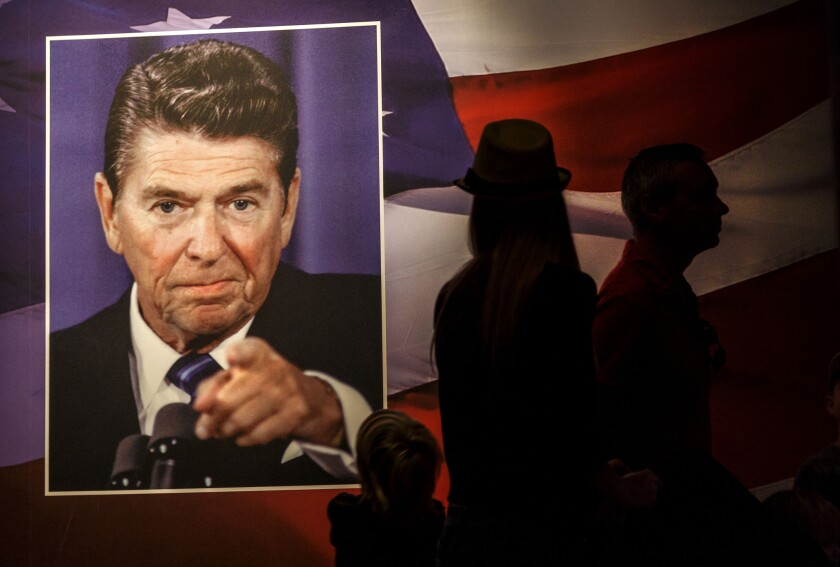 Visitors silhouetted against an image of the American flag and former U.S. President Ronald Reagan at the Ronald Reagan Presidential Library on February 16.