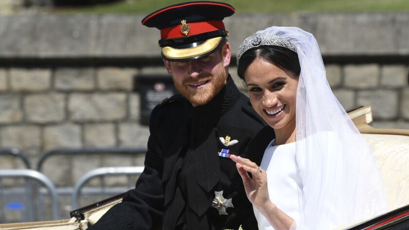 Britain's Prince Harry, Duke of Sussex and his wife Meghan Markle, Duchess of Sussex wave from the A