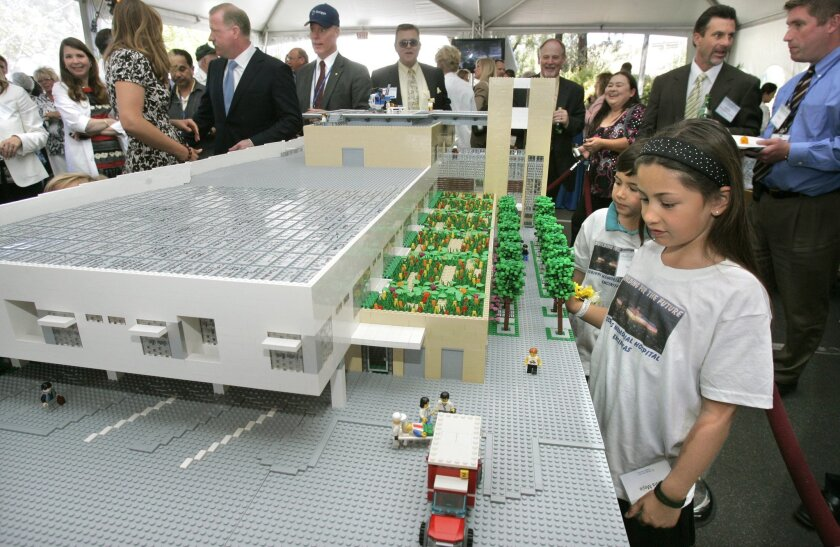 Olivia Mejia and her brother, Nolan, looked at a Lego model of the planned critical-care building at Scripps Memorial Encinitas yesterday during a ceremony at the hospital.