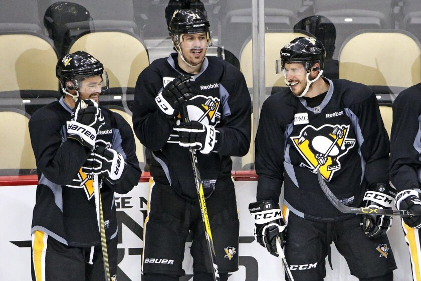 Pittsburgh Penguins' Chris Kunitz, left, Evgeni Malkin (71) and Sidney Crosby (87) wait to run a drill during hockey practice at the Consol Energy Center in Pittsburgh, Sunday May 29, 2016. The Penguins are preparing for Game 1 of the Stanley Cup finals against the San Jose Sharks on Monday, May 30