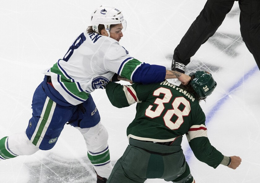 Minnesota Wild's Ryan Hartman (38) and Vancouver Canucks' Jake Virtanen (18) fight during the first period of an NHL hockey playoff game Friday, Aug. 7, 2020, in Edmonton, Alberta. (Jason Franson/Canadian Press via AP)