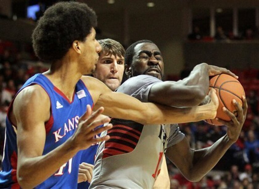 Kansas' Kevin Young and Jeff Withey battle for the rebound with Texas Tech's Kader Tapsoba during an NCAA college basketball game in Lubbock, Texas, Saturday, Jan. 12, 2013. (AP Photo/Lubbock Avalanche-Journal,Stephen Spillman)