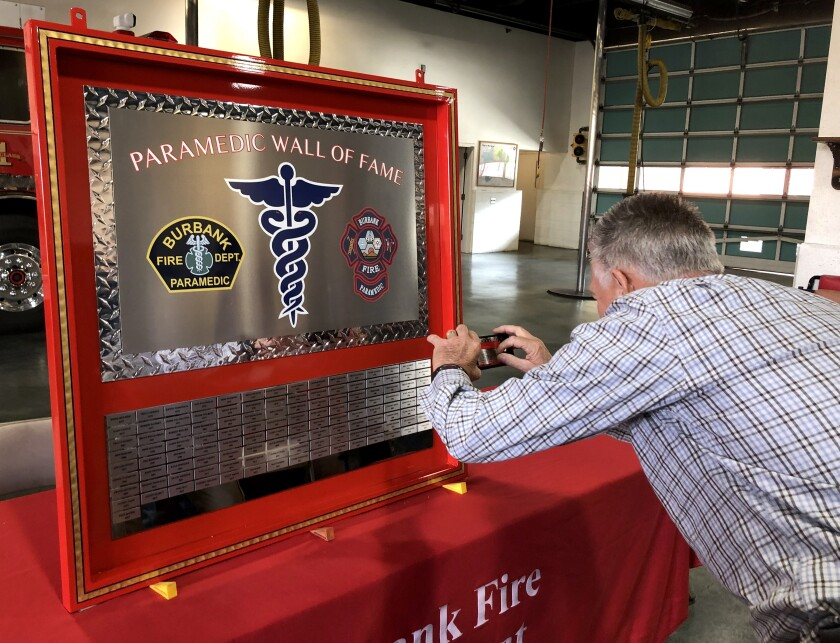 Retired Fire Capt. Robert Reinhardt takes a photo of his name on the Burbank Fire Department's Paramedic Wall of Fame that was unveiled on Thursday at the agency's headquarters.