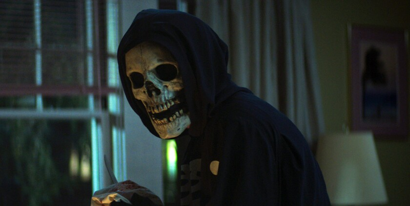 A figure in a skull mask and hoodie in a house at night