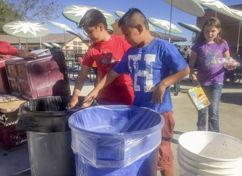 Del Rio Elementary School fourth graders Gabriel Palacios, left, and Jhosmar Martinez sort lunch recyclables, as classmate Kaitlin Kuhn, right, approaches to deposit more recyclables.
