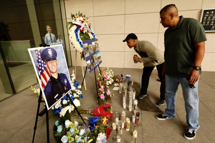 LAPD Officer Juan Jose Diaz in uniform with American flag behind him