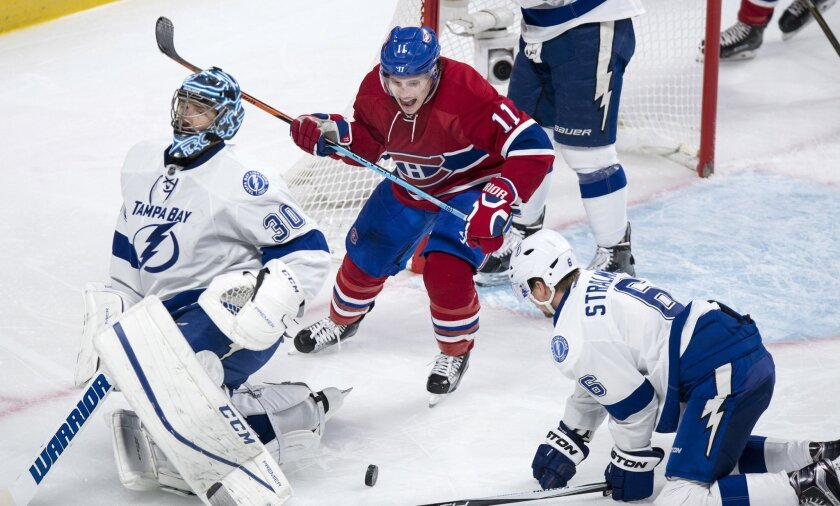 Montreal Canadiens' Brendan Gallagher (11) celebrates a goal by teammate Tomas Plekanec, not shown, next to Tampa Bay Lightning goalie Ben Bishop and Anton Stralman during the third period of an NHL hockey game, Tuesday, Feb. 9, 2016, in Montreal.  (Paul Chiasson/The Canadian Press via AP) MANDATOR