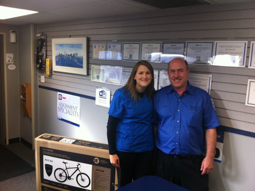 Nurse Jessica Gutsche picks up her replacement bicycle (in box) from David Ely, owner of Convoy Auto Repair.