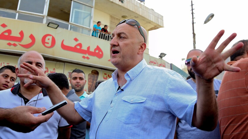 Majed Hattar, brother of Jordanian journalist Nahedh Hattar, speaks to reporters during a sit-in in the town of Al-Fuheis, near Amman, Jordan on Sunday.