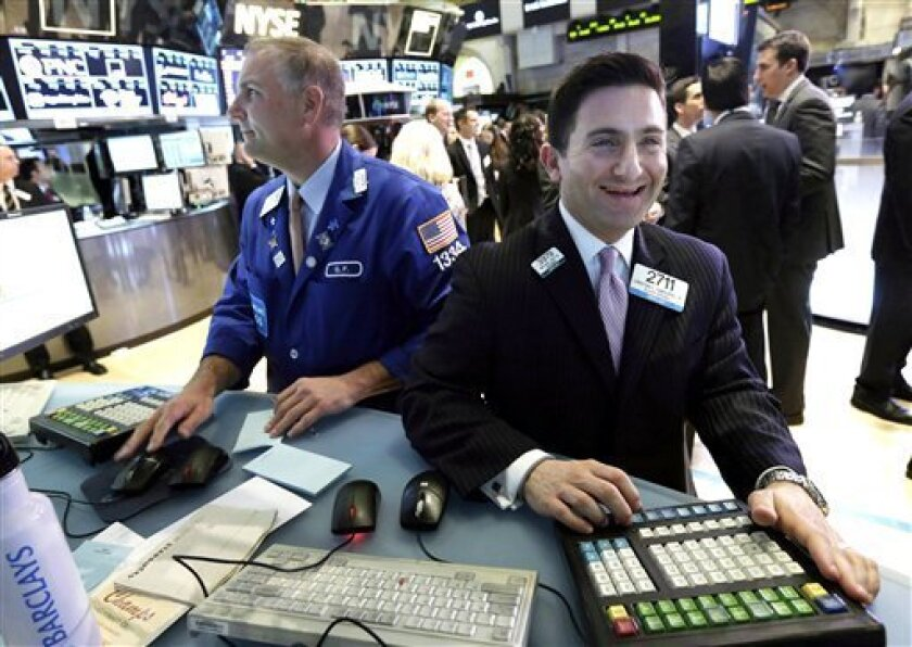 FILE - In this Tuesday, March 5, 2013, file photo, specialist Christian Sanfillippo, right, smiles as he works at his post on the floor of the New York Stock Exchange. The Dow's new all-time high and better economic data from the United States propelled world stock markets higher Wednesday March 6, 2013. (AP Photo/Richard Drew, File)