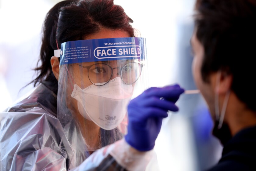 Nursing student Kathryn Domingo, in face mask and shield, gives a COVID-19 test to a person.