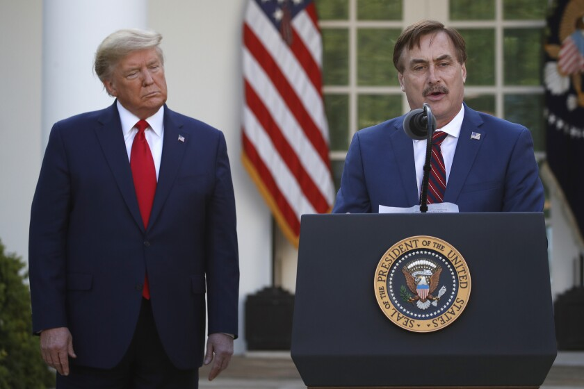 President Trump listens as Mike Lindell, CEO of My Pillow, speaks at the White House last March.