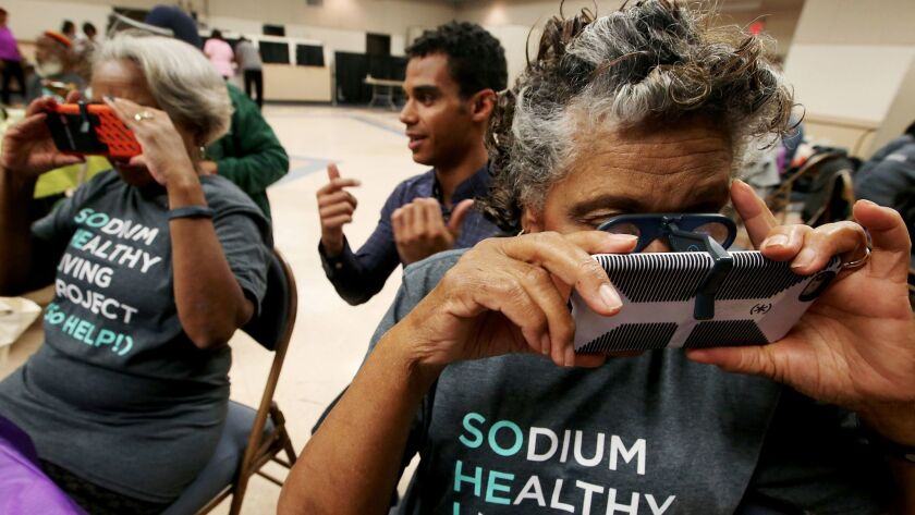 Technician Ryan Anderson, center, helps Sodium Healthy Living Project participants Sandra Goldsmith, 74, left, and Blanche Ross, 83, use their mobile phones to view a virtual reality video telling them about different foods and their sodium content.