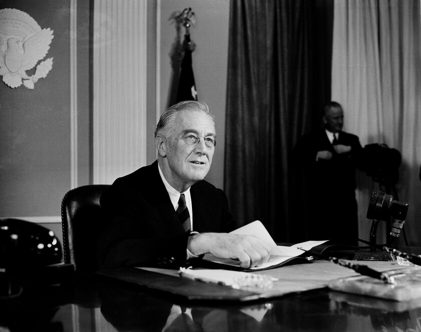Roosevelt, in suit and tie, sits at a desk with one hand on some papers.
