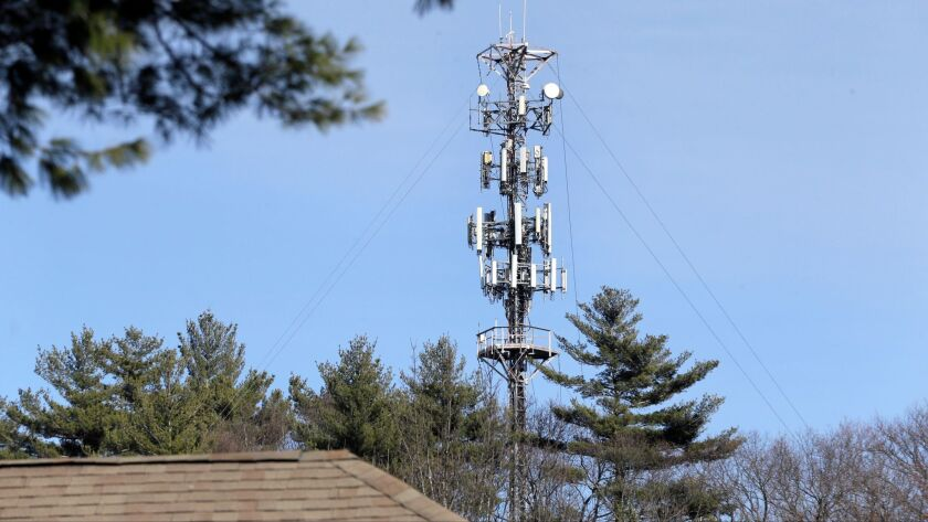 In this March 13, 2017 photo, a cell tower is seen through trees in North Andover, Mass. Insurance c